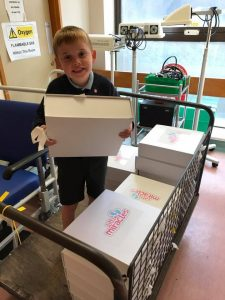 Harry age (6) delivering boxes at SCUBU